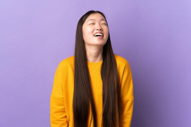 笑っている孤立した紫色の壁の上の若い中国の女の子