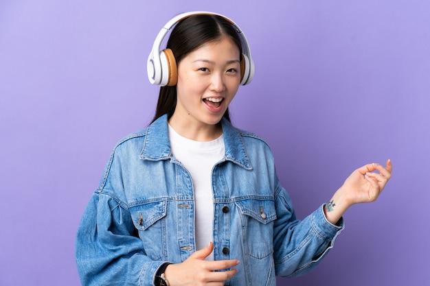 音楽を聴き、ギターのジェスチャーをしている孤立した紫色の壁の上の若い中国の女の子