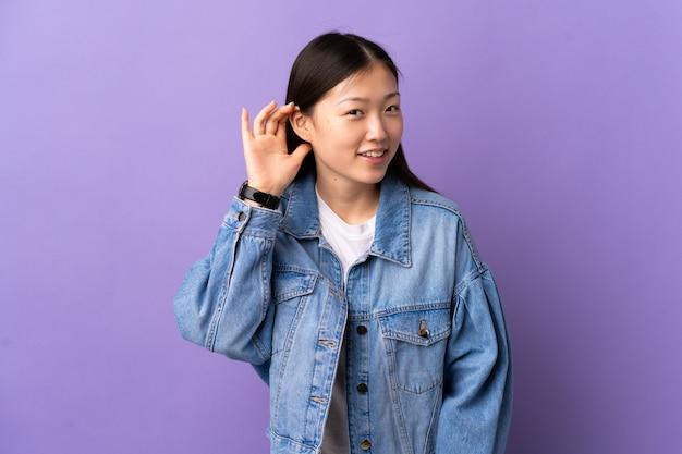Молодая китайская девушка над изолированной фиолетовой стеной слушая что-то кладя руку на ухо