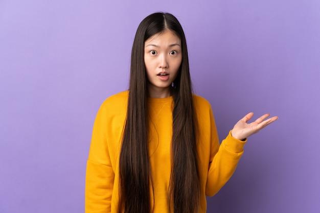 의심 제스처를 만드는 고립 된 보라색 벽 위에 젊은 중국 소녀