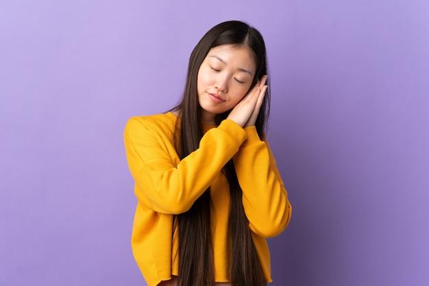 愛らしい表情で睡眠ジェスチャーをしている孤立した紫色の壁の上の若い中国人の女の子
