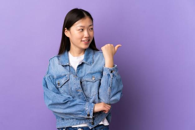 Молодая китаянка над изолированной фиолетовой стеной, указывая в сторону, чтобы представить продукт