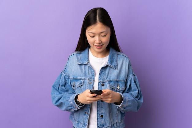 Молодая китаянка над изолированной фиолетовой стеной отправляет сообщение по мобильному телефону