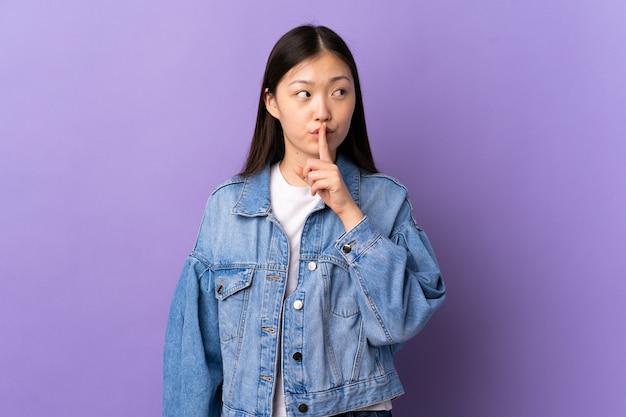 Молодая китаянка над изолированной фиолетовой стеной показывает знак жеста молчания, кладя палец в рот