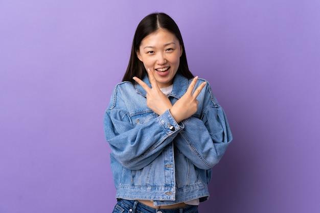 笑顔と勝利のサインを示す孤立した紫色の壁の上の若い中国の女の子