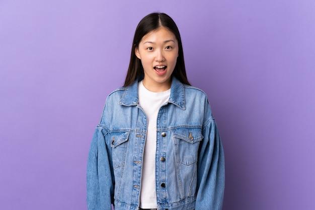 驚きの表情で孤立した紫色の壁の上の若い中国の女の子