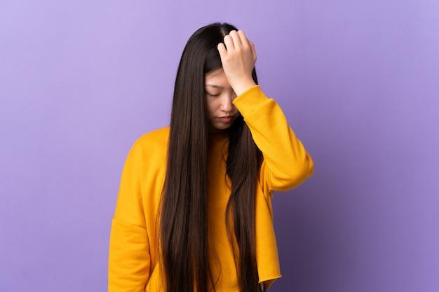 Молодая китайская девушка над изолированным пурпуром с головной болью