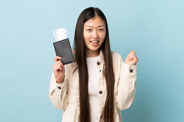 Молодая китайская девушка над изолированной стеной счастливая в каникулах с паспортом и билетами на самолет