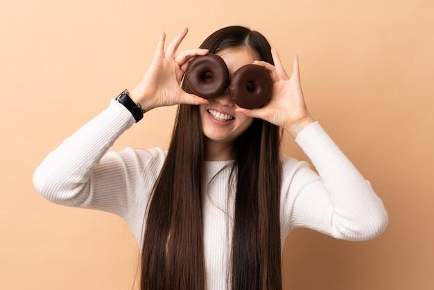 目にドーナツを保持している孤立した壁の上の若い中国の女の子
