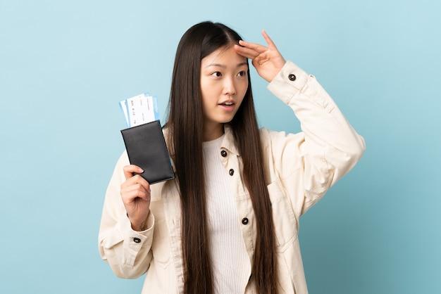 遠くで何かを見ながらパスポートと飛行機のチケットで休暇中に孤立した壁を越えて若い中国の女の子