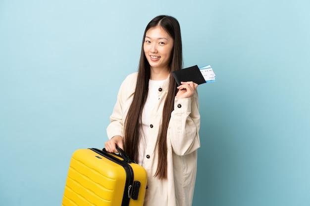 Молодая китаянка над изолированной стеной в отпуске с чемоданом и паспортом