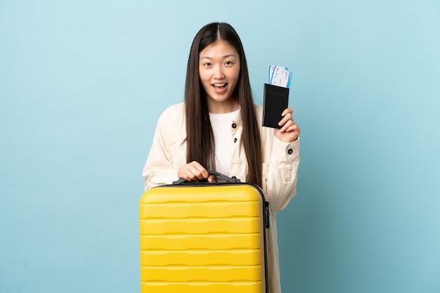 スーツケースとパスポートと休暇で孤立した壁を越えて若い中国の女の子