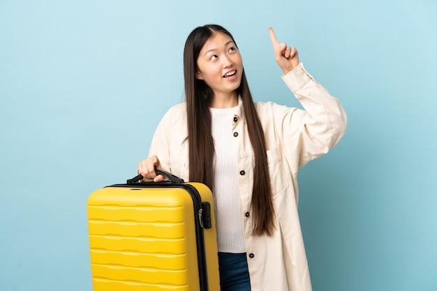 Молодая китаянка над изолированной стеной в отпуске с дорожным чемоданом и указывая вверх