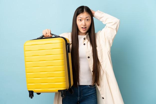 여행 가방 휴가에 고립 된 벽을 통해 젊은 중국 여자와 놀