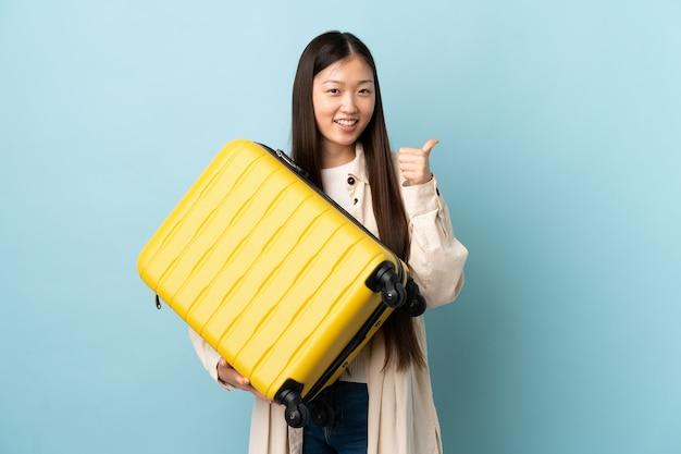旅行スーツケースと親指を上にして休暇で孤立した壁を越えて若い中国の女の子