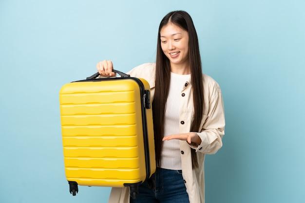 旅行スーツケースと休暇で孤立した壁の上の若い中国の女の子
