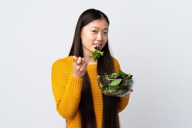 幸せな表情でサラダのボウルを保持している孤立した白い背景の上の若い中国の女の子