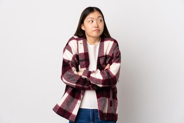 어깨를 드는 동안 의심 제스처를 만드는 격리 된 흰색 배경 위에 젊은 중국 소녀