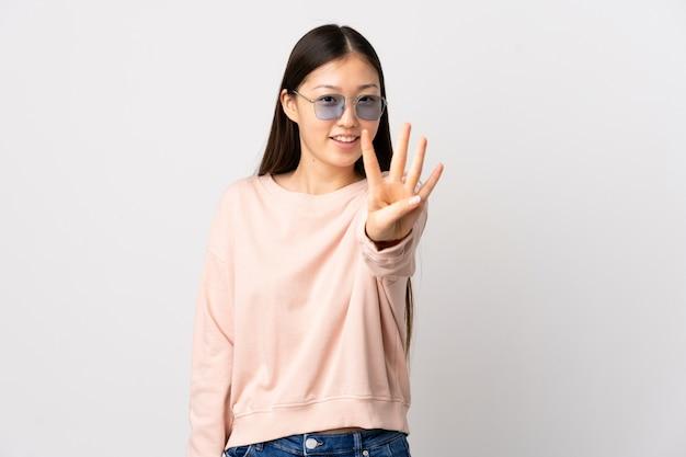 Молодая китайская девушка над изолированным белым счастливым и подсчитывать 4 с пальцами