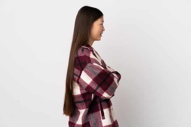横の位置で孤立した白の上の若い中国の女の子