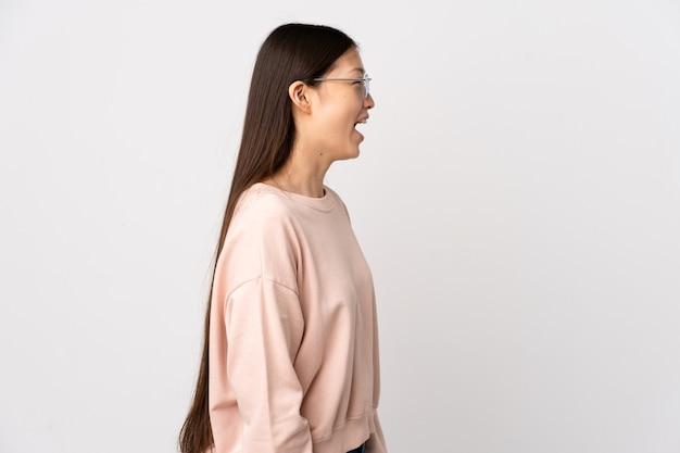 横向きの位置で笑っている孤立した白い上の若い中国の女の子