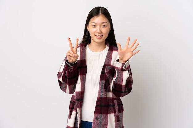指で7を数える孤立した白い壁の上の若い中国の女の子