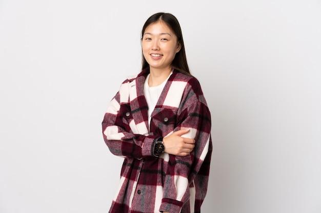 笑っている孤立した白い壁の上の若い中国の女の子