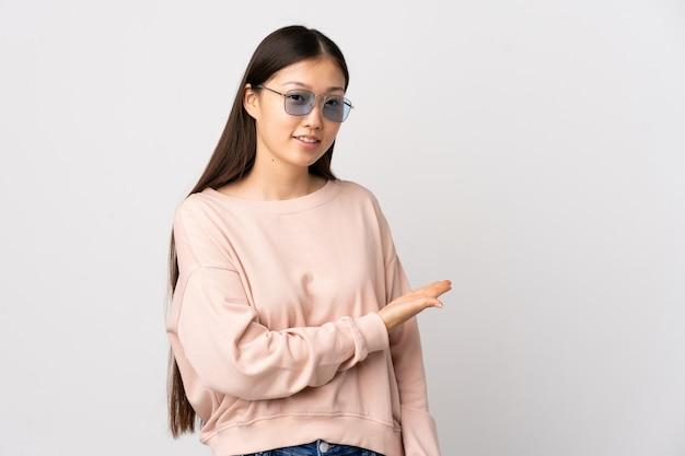 に向かって笑顔を見ながらアイデアを提示する孤立した白い壁の上の若い中国の女の子