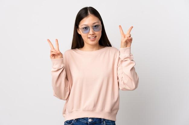 両手で勝利のサインを示す孤立した白い壁の上の若い中国の女の子