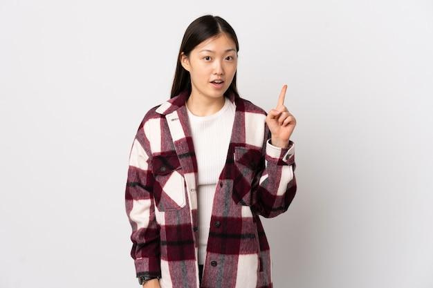 指を上に向けるアイデアを考えている孤立した白い壁の上の若い中国の女の子