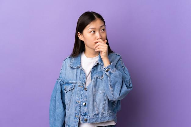 보라색 의심을 가지고 혼란스러운 얼굴 표정으로 어린 중국 소녀
