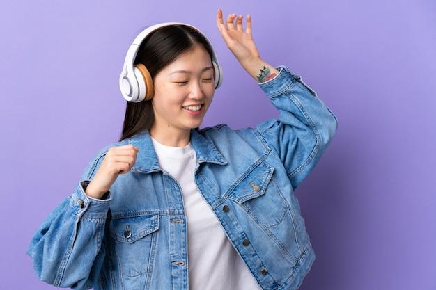 Молодая китаянка над фиолетовым слушает музыку и танцует