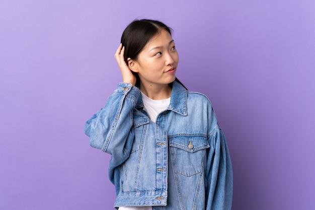 アイデアを考えて紫色の若い中国の女の子