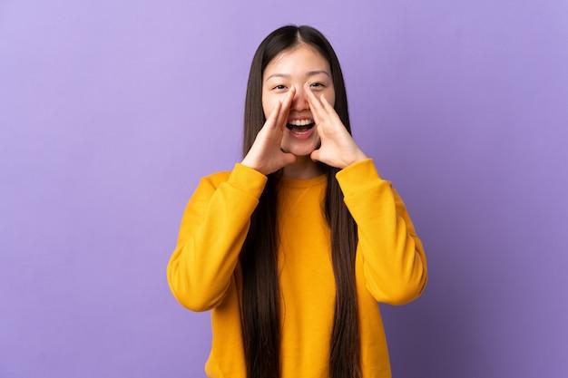 叫び、何かを発表する紫色の壁を越えて若い中国の女の子