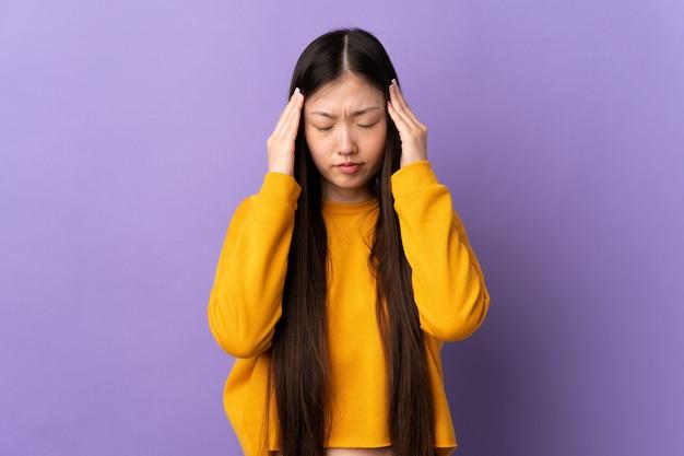 Молодая китайская девушка над фиолетовой стеной с головной болью