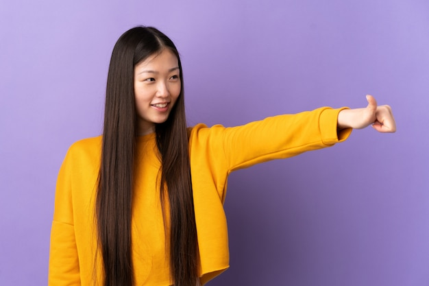 Young chinese girl over purple wall giving a thumbs up gesture
