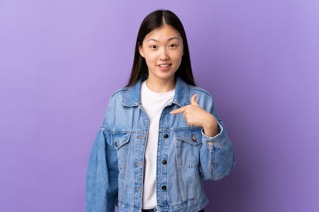 Young chinese girl over purple wall with surprise facial expression