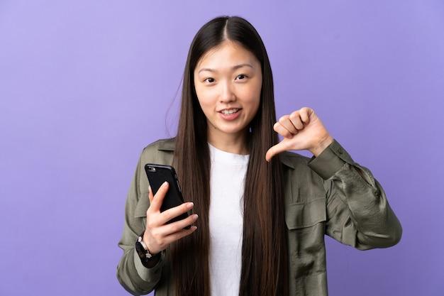 Молодая китайская девушка с помощью мобильного телефона изолирована