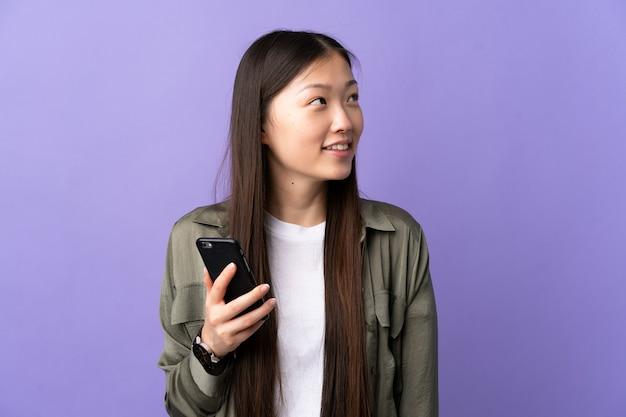 Молодая китайская девушка, использующая мобильный телефон над изолированным фиолетовым, смотрит вверх, улыбаясь