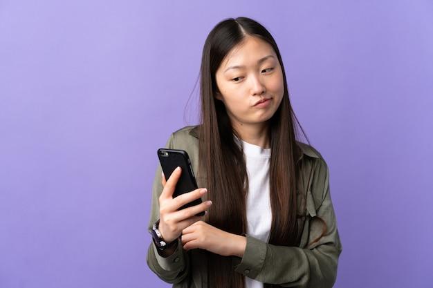 슬픈 표정으로 고립 된 보라색 벽 위에 휴대 전화를 사용하는 어린 중국 소녀