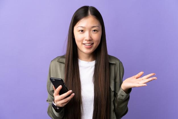 Молодая китаянка с шокированным выражением лица разговаривает по мобильному телефону над изолированной фиолетовой стеной