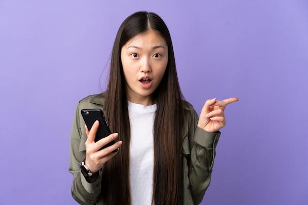 Молодая китаянка с помощью мобильного телефона над фиолетовым удивлена и указывает сторону