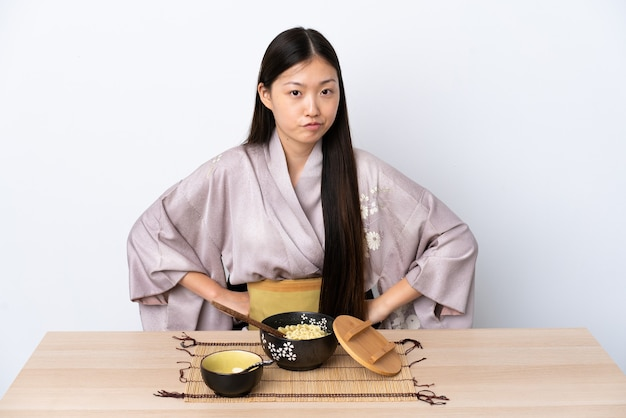 Молодая китайская девушка в кимоно и сердится на лапшу