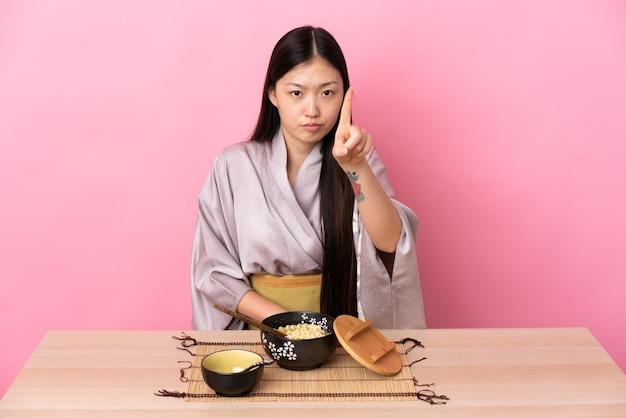 Молодая китаянка в кимоно ест лапшу, считая одного с серьезным выражением лица