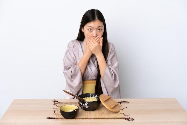 Молодая китаянка в кимоно и ест лапшу, прикрывая рот руками