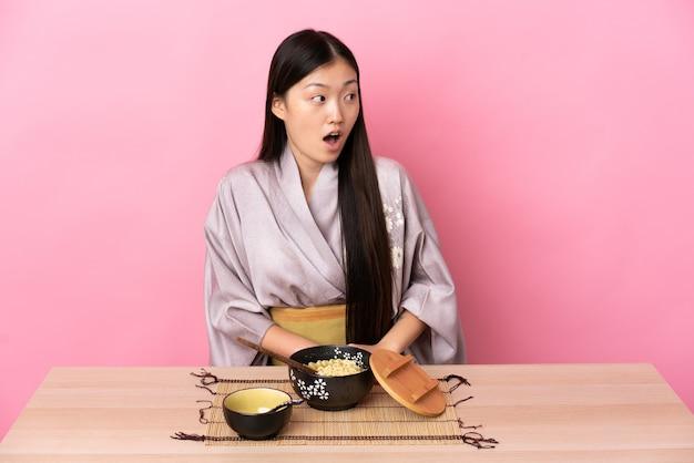 Молодая китайская девушка в кимоно и ест лапшу, делая неожиданный жест, глядя в сторону