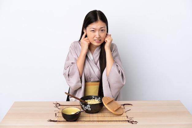 Молодая китаянка в кимоно, разочарованная и закрывающая уши ест лапшу