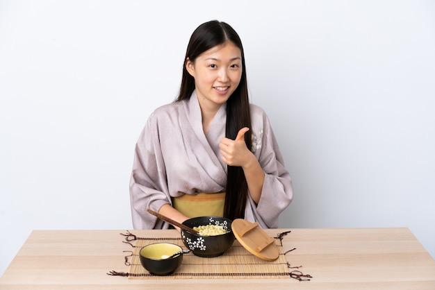 Молодая китаянка в кимоно и ест лапшу, показывая большой палец вверх