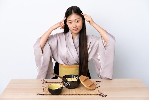 Молодая китайская девушка в кимоно и ест лапшу, сомневаясь и думая