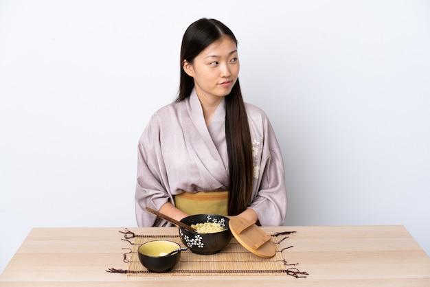 기모노를 입고 측면을 보면서 의심을 가진 국수를 먹는 어린 중국 소녀